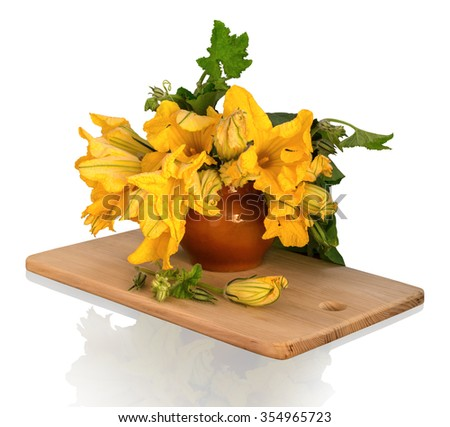Still Life in potpourri style. Magnificent bouquet of huge orange flowers pumpkin with leaves and buds in ancient clay pot on wooden chopping board isolated on white background with clipping path - stock photo