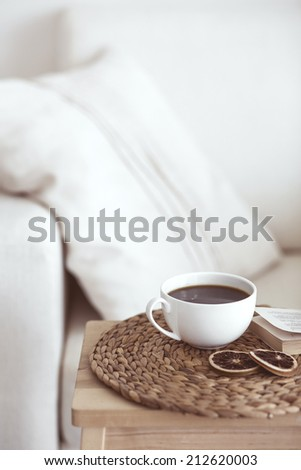 Still life interior details, cup of coffee and a book near white cozy chair - stock photo