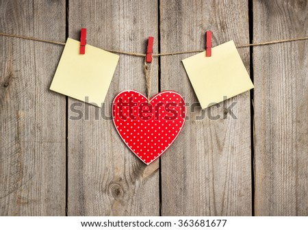 Still life, love and holidays concept. Red heart and card hanging on the clothesline for Valentines Day. Selective focus, copy space rustic wooden background - stock photo