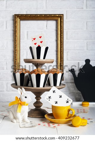 Still life Mad tea party with bunny and muffins - stock photo