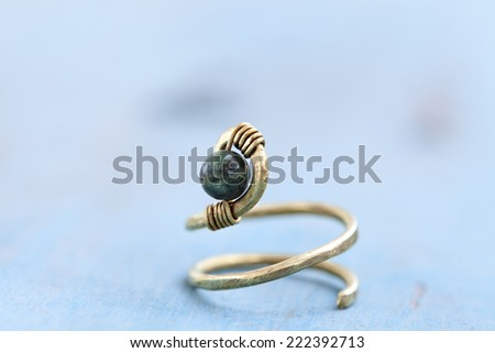 Still life of a hand made tribal ethnic ring resting on light blue background. - stock photo