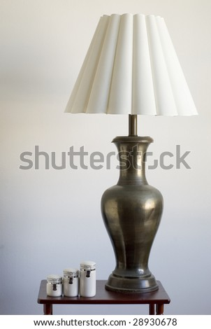 Still life of a large table lamp and matching porcelain containers on a small table. - stock photo
