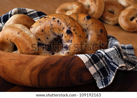 Still life of assorted bagels (blueberry, whole wheat, and cinnamon) in wooden bowl with handwoven cloth.  Additional bagels in soft focus in background.  Closeup with shallow dof. - stock photo