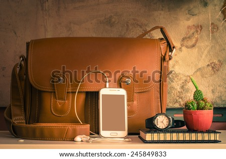 Still life of bag and stationary on table at home - stock photo