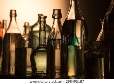 Still Life of Bottles in the homemade distillery cellar. - stock photo