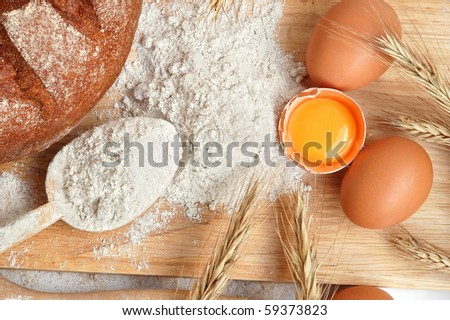 Still life of bread, eggs, cereas, flour and kitchen tools on a wooden board - stock photo