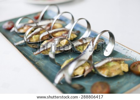 still life of ceramic green dish tray with delicious anchovies with guacamole and tomato in metal curved spoons on restaurant white table - stock photo