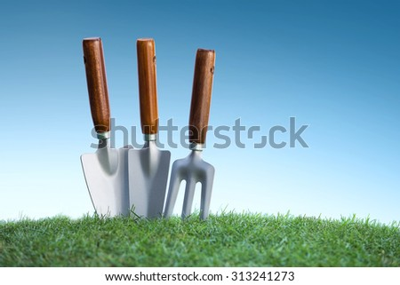still life of close up gardening tools on green grass under bright blue sky - stock photo