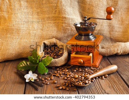 Still life of coffee beans in jute bag with coffee grinder and coffee cup on a wooden table  - stock photo