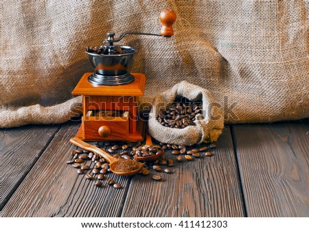 Still life of coffee beans in jute bag with coffee grinder on a wooden table  - stock photo