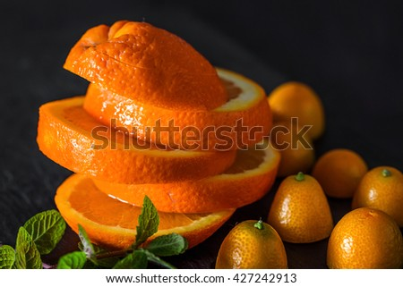 Still life of cut segments of orange with halved tangerines and branch of mint - stock photo