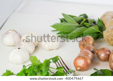 still life of garlic onion pepper and basil on white background - stock photo