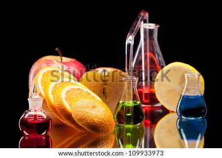Still life of laboratory glassware with colorful liquids and fruits on black background - stock photo