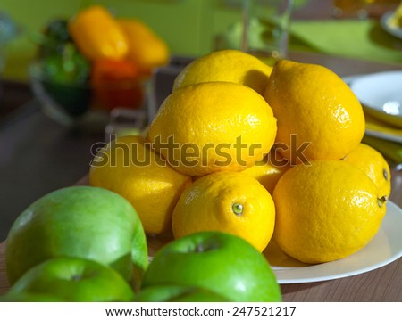 still life of lemons and apples on kitchen wooden table with a small depth of field - stock photo