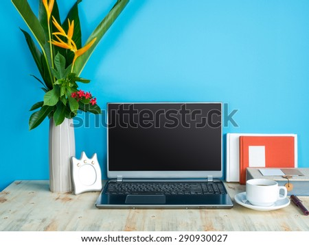Still life of modern colorful interior workspace with laptop, flower vase, coffee cup - stock photo