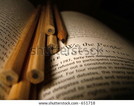 Still life of pencils and a book on the writing of the constitution. - stock photo