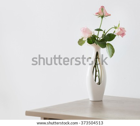 still life of pink rose in ceramic vase - stock photo