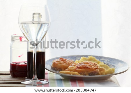 Still life of red wine glass, soy sauce bottle, fruit sauce jar and roasted meat slices with mashed potato   - stock photo