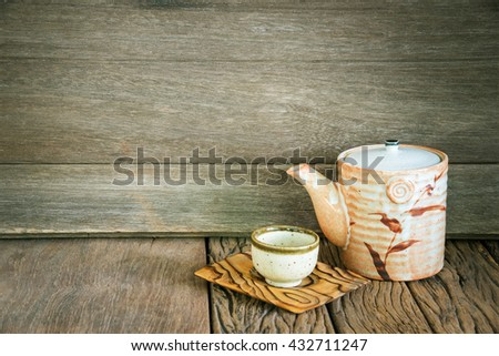 Still life of set of japanese ceramic teapot and cup on wooden texture background. - stock photo