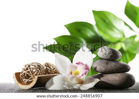 Still life of spa stones on bamboo mat surface with green leaves isolated on white - stock photo