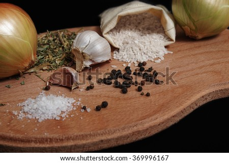Still life of spices and rice on a black background - stock photo