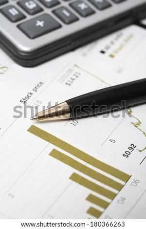 Still life of stock market stats calculator and pen  - stock photo