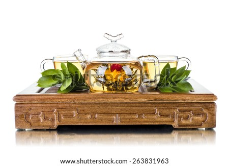 still life of the glass teapot flow green tea in cup on wooden trivet, white background, isolated,  tea ceremony - stock photo