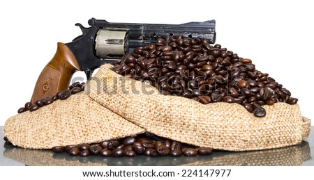 Still life of toy gun with a pile of coffee beans on the cap and floor reflections. - stock photo