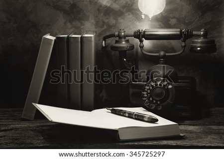 Still life of vintage telephone on table with diary book, Black and White image - stock photo