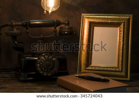 Still life of vintage telephone with picture frame and diary on table - stock photo