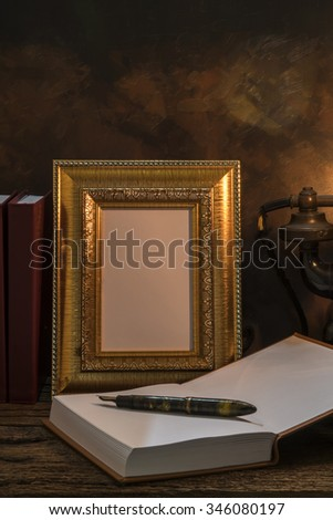 Still life of vintage telephone with picture frame and diary on table, focus at the frame - stock photo