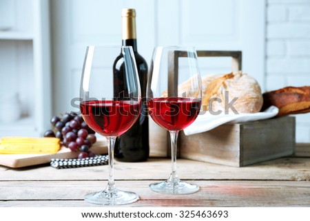Still life of wine, grape, cheese and bread on light background - stock photo