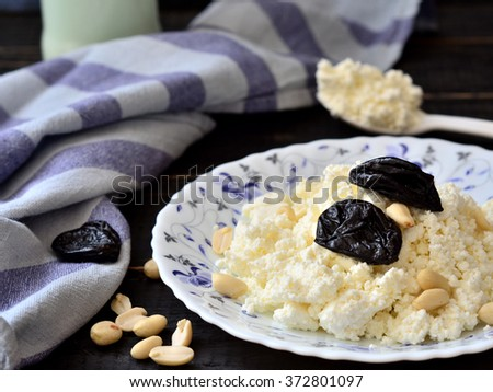 Still Life on a dark background - curd with prunes and milk on a plate - stock photo