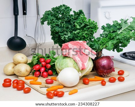 Still life on a kitchen table wooden board, ingredients for soup: green leaves of kale, red and white onion, radish, white potato, cabbage head, tomato, carrot, raw meat, organic healthy food - stock photo