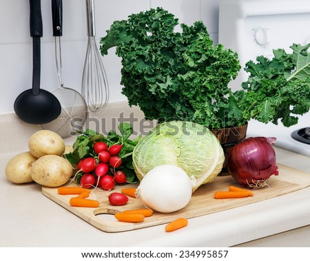 Still life on a kitchen table wooden board, ingredients for soup: green leaves of kale, red and white onion, radish, white yellow potato, cabbage head, carrot, organic healthy food - stock photo