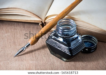 still life, opening vintage book on wooden table with quill pen and inkwell - stock photo