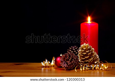 Still life photo of a Christmas candle burning bright with gold pine cones and ribbon plus a red bauble, copy space on the black background to add your own text. - stock photo