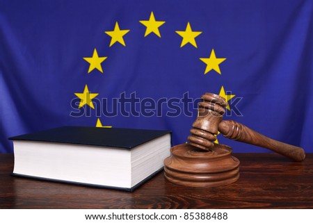 Still life photo of a gavel, block and law book on a judges bench with the European Union flag behind. - stock photo