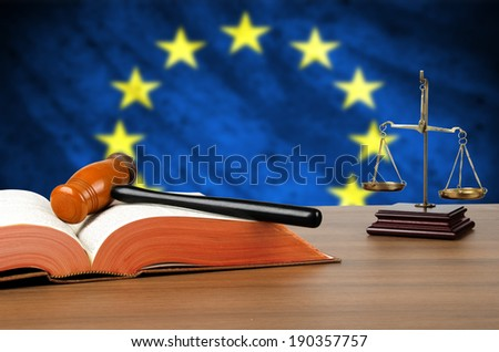 Still life photo of a gavel, scales of justice and law book on a judges bench with the European Union flag behind.  - stock photo