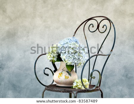 Still Life photo with Hortensia Flowers on rusty Chair - stock photo