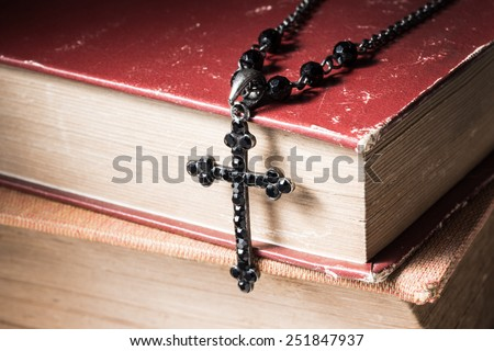 still life photography : faith concept with close up of old bible and old cross necklace - stock photo