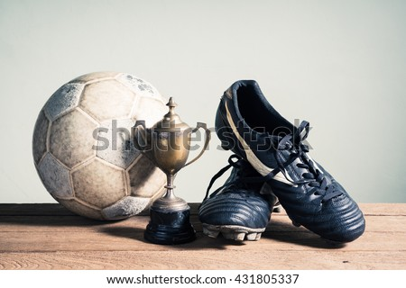 still life photography : old football, football shoes and trophy on old wood table in championship concept - stock photo