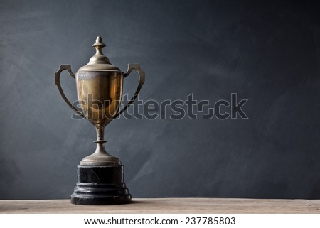still life photography :  old trophy on old wood with space of art dark background - stock photo