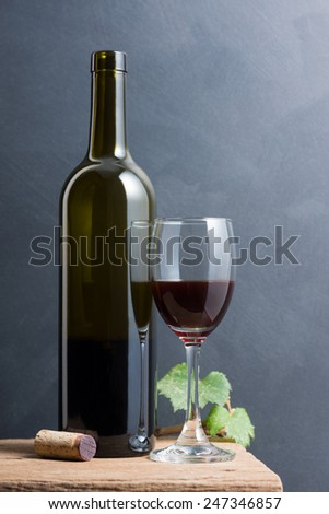 still life photography : red wine in bottle and glass with grape leaf and cork on old wood  with dark art background - stock photo