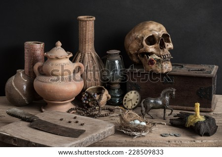 still life photography, skull with dry rose in the mouth and wooden box, candle, chopping block, clock, metal horse, egg, old knife, lantern, nest, pottery, rosary and wicker - stock photo
