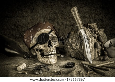 Still life, pirate skull with cigar in the mouth on the log, compass on ancient map, knife brass tea pot and pocket watch - stock photo