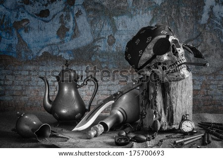 Still life, pirate skull with cigar in the mouth on the log, compass on ancient map, knife brass tea pot and pocket watch with grunge wall background - stock photo