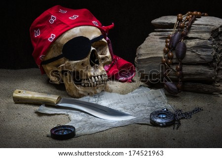 Still life, pirate skull with knife, compass on floor and pocket watch on the floor - stock photo