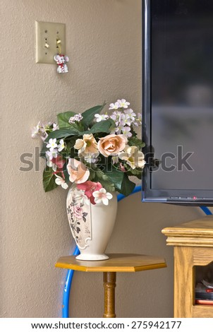 Still life plastic flowers vase stand and TV corner. - stock photo