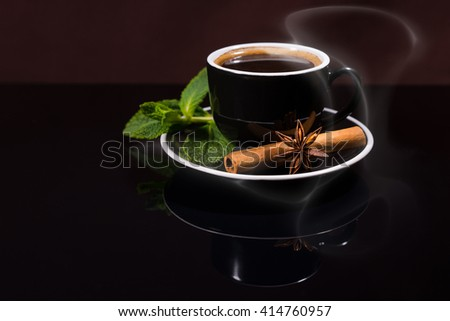 Still Life Profile of Cup of Steaming Hot Black Coffee Served on Saucer with Fresh Sprig of Mint, Cinnamon Stick and Star Anise on Shiny Black Table Surface with Copy Space - stock photo